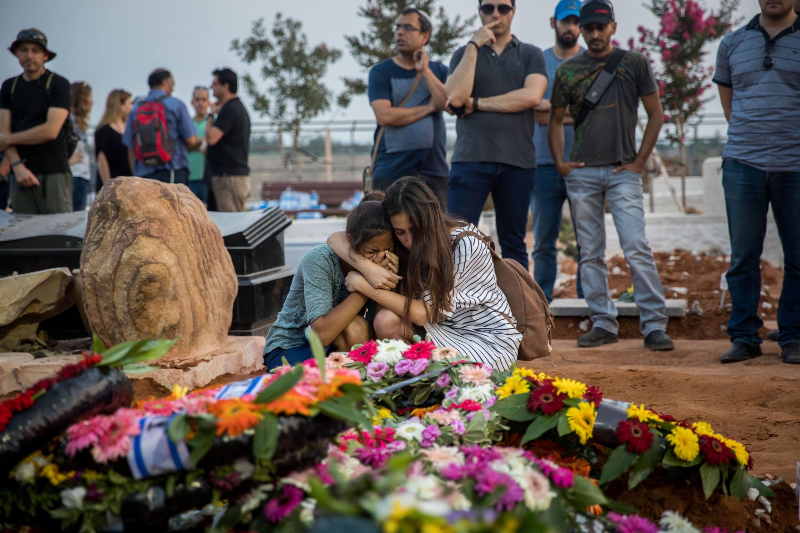 Friends and relatives mourn at the graves of Yosef Salomon (70), his daughter Haya (46) and son Elad (35), after their funeral, attended by thousands, at the Modiin Cemetery, on July 23, 2017. The Salomon family members were murdered in a stabbing attack by a Palestinian youth who attacked them during their Friday night dinner at their home in the Jewish settelment of Halamish in the West Bank. Photo by Yonatan Sindel/Flash90 *** Local Caption *** çìîéù ôéâåò çìàîéù ã÷éøä éåñó ñìåîåï (70) åùðé éìãéå çéä (46) åàìòã (35) ìååéä ðøöçéí äøåâéí áéú òìîéï îåãéòéï