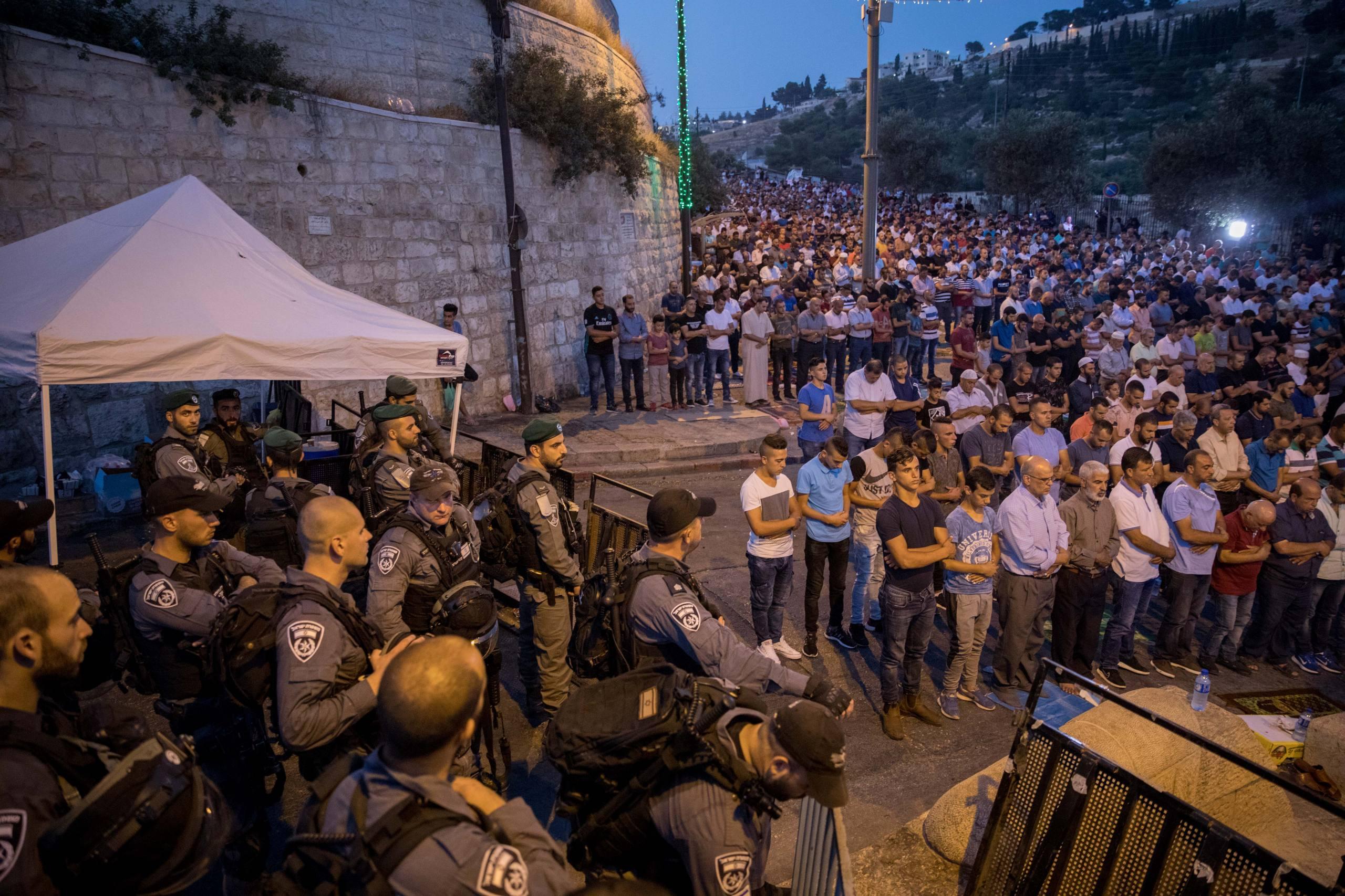 """Israeli police guard as Muslim worshipers perform their evening prayers near the Lion's Gate, outside the Temple Mount, in Jerusalem's Old City on July 24, 2017. Photo by Yonatan Sindel/Flash90 *** Local Caption *** äø äáéú áéãå÷ îùèøä úôéìä ùåèøéí îâ""""á îúôììéí îåñìîéí"""