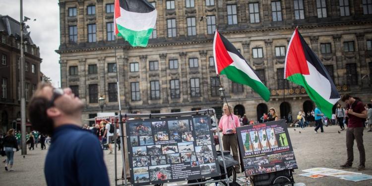 People look at a BDS stand with photos and Palestinian flags, calling to 'Free Palestine' at Dam Square in central Amterdam, Holland, on June 24, 2016. Photo by Hadas Parush/Flash90 *** Local Caption *** àîñèøãí äåìðã àéøåôä úééøåú úééøéí èéåì çøí áé ãé àñ ôìñèéï ôìñèéðéí éùøàì ôøå ôìñèéðàé àðèé éùøàì éùøàìéí