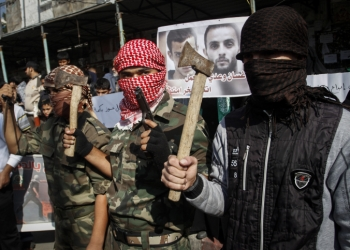 Masked Palestinians hold axes and a gun as they celebrate with others an attack on a Jerusalem synagogue, in Rafah in the southern Gaza Strip, on November 18, 2014. Two Palestinians armed with a meat cleaver and a gun killed four people in a the Bnei Torah synagogue in Jerusalem's Har Nof neighborhood on Tuesday before being shot dead by police. This was the deadliest attack in six years in the Jerusalem, and comes after a series of car-ramming and stabbing terror attacks in Israel. Photo by Abed Rahim Khatib/Flash90 *** Local Caption *** ???????? ?????? ????? ????? ???? ??? ??? ???? ??? ???? ?? ??? ??????? ??? ????? ??? ???? ???? ??? ???? ???? ?????? ?????? ??????