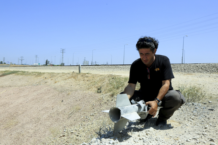 A man holds a rocket that had exploded and fallen near the Border with the Gaza Strip on August 20, 2014, Israel and Palestinian militants resumed fire across the Gaza border, sparking panic across the war-torn enclave and halting truce talks. Photo by Edi Israel/Flash90 *** Local Caption *** ???? ??? ???? ????? ?? ????? ??? ????? ??? ?????
