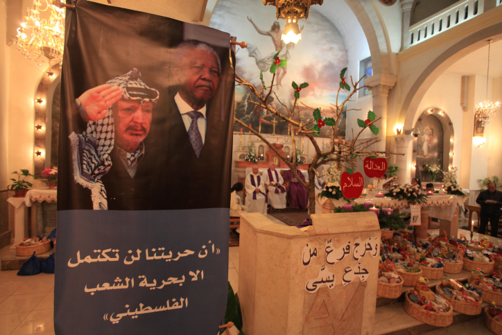 An image of the late South African leader President Nelson Mandela on display during a special Sunday service in his honor at the Holy Family Church in the West Bank city of Ramallah on December 8, 2013. Mandela, South Africa's first black president who steered his nation out of apartheid and into multi-race democracy, died late on December 5, at the age of 95 after months of illness. Photo by Issam Rimawi/Flash 90  *** Local Caption *** ????? ????? ?????? ???? ???? ?????? ??????? ???? ??????? ??????