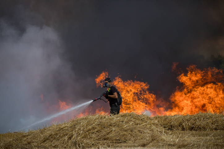 Israeli firefighters extinguish a fire in a wheat field caused from kites flown by Palestinian protesters, near the border with the Gaza Strip, May 30, 2018. Photo by Yonatan Sindel/Flash90 *** Local Caption *** ??? ???? ???? ????? ??? ??? ??? ??????