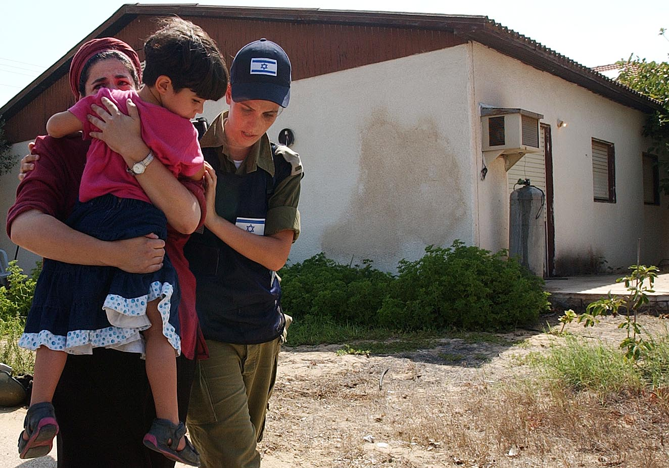 An Israeli soldier women evacuate a Jewish settler woman holding her child from a settlement during the pullout plan in the settlement of Neve Dekalim. Photo by Pierre Terdjamn/Flash90. *** Local Caption *** ??? ????? ??????? ??? ???? ??? ??????? ???????? ??????? ??? ???? ????? ????? ???????