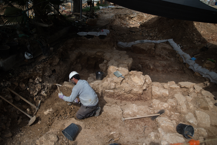 A man digging at a digging site of the remains of a Large Impressive Winery and a Roman Bathhouse near a construction site in Jerusalem's Schneller Compound on March 2, 2016. Unexpected finds more than 1,600 years old were uncovered during archaeological excavations financed by the Merom Yerushalayim Company, which the Israel Antiquities Authority is carrying out in Schneller Compound prior to the construction of residential buildings for Jerusalem's ultra-orthodox population. Interesting and assorted finds from Jerusalem's past were discovered in the archaeological excavation, most notably a large and impressive winery dating to the Roman or Byzantine period, some 1,600 years ago. The complex installation includes a pressing surface paved with a white mosaic. Photo by Yonatan Sindel/Flash90 *** Local Caption *** ???? ??????????? ????????? ?????? ??? ????? ???? ?????? ??? ????? ??? ??????