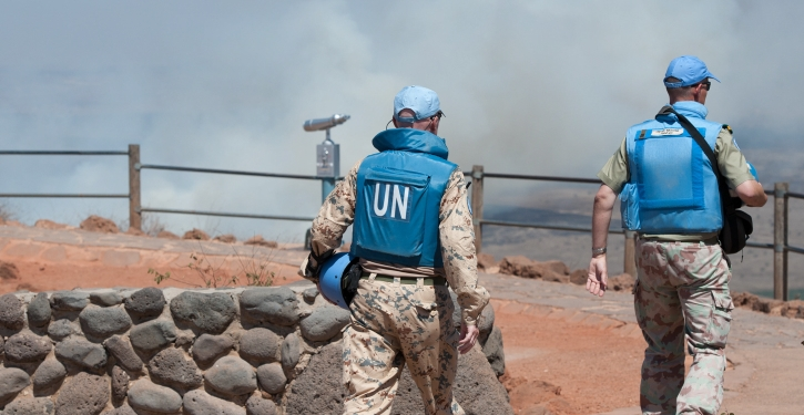 UN soldiers walk as Smoke rises near Quneitra Crossing as it seen from the Golan Heights in the Israeli side on August 27, 2014, The IDF instructed farmers and civilians on Wednesday to stay away from the border with Syria on the Golan Heights. The measure came after intense fighting between the Syrian army and rebels in the Quneitra  crossing region. Photo by Flash90   *** Local Caption *** ???? ????? ????? ??? ?? ???? ???? ?????? ???? ???? ??????? ????? ????? ?????