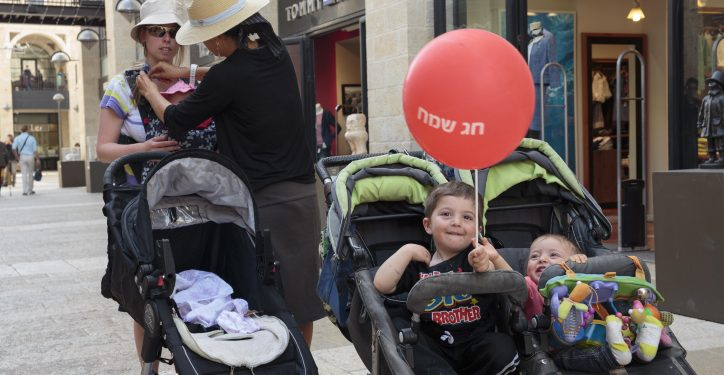 "A boy holds a balloon reading ""Happy Holidays"" while in the Mamilla Mall shopping center in Jerusalem on March 13, 2013. Photo by Sarah Schuman/FLASH90 *** Local Caption *** ????? ?? ??? ????"