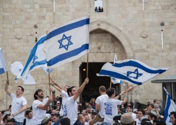 Thousands of Jewish wave the Israeli flags as they celebrate Jerusalem Day by dancing through Damascus Gate on their way to the Western Wall. Jerusalem Day celebrations mark the 51th anniversary of its capture of Arab east Jerusalem in the Six Day War of 1967. May 13, 2018. Photo by Yonatan Sindel/Flash90 *** Local Caption *** ??? ??????? ??????  ??? ?????  ?????  ???? ????? ??? ???