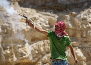 """Palestinian shooting a flare throw stones at Israeli policemen during protests in the east Jerusalem Arab neighborhood of Issawiya on May 15, 2012, marking Nakba day, the day when Palestinians mark """"Nakba"""", or catastrophe, of Israel's founding in a 1948 war. Photo by  Noam Moskowitz /Flash90 *** Local Caption *** ??????? ???????? ??????? ???????? ??????? ??????? ???? ?????? ???? ????? ???? ??????? ???"""