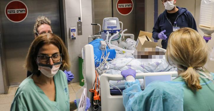 Ichilov Workers wearing masks as they move a patient to a new ward at the Ichilov Hospital in Tel Aviv, March 22, 2020. Photo by Yossi Zamir/Flash90 *** Local Caption *** ?????? ????? ????? ??? ????? ????? ????? ???????