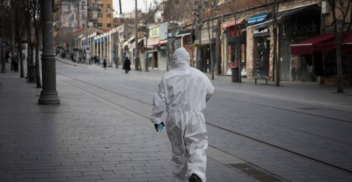 A man wearing protective clothes for fear of the coronavirus walks in Jaffa street in downtown Jerusalem on March 20, 2020. Photo by Nati Shohat/Flash90 *** Local Caption *** ???? ???? ?????? ????? ?????? ????? ???? ???