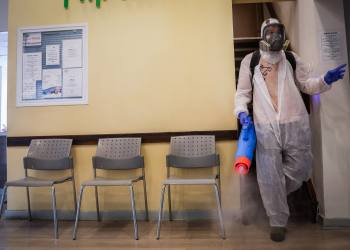 Workers wearing protective clothes disinfect a shop in Jerusalem, on March 15, 2020, as part of measures to prevent the spread of the Coronavirus. Photo by Yonatan Sindel/Flash90 *** Local Caption *** קורונה וירוס ירושלים עובדים בניין חיטוי