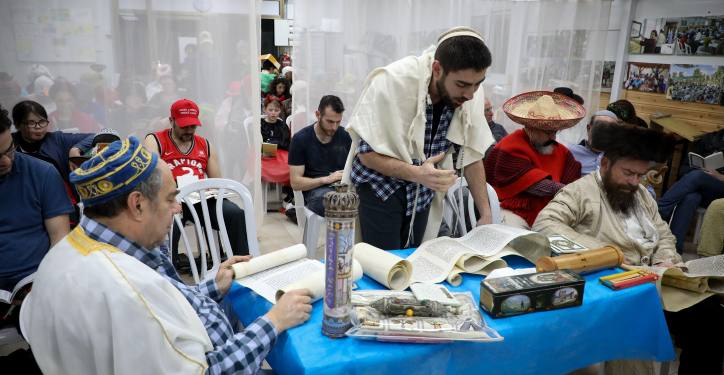 Jewish Israelis read the Megillat Esther (the Story of Esther) as they wear costumes during the Jewish holiday of Purim, in Oz Vegaon in Gush Etzion, on March 9, 2020. Photo by Gershon Elinson/Flash90 *** Local Caption *** ????? ????? ???? ???? ????? ??? ???? ??? ?????  ?????