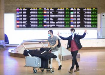 People wear face masks for fear of the corona virus as they arrive at the Ben Gurion International Airport on March 11, 2020. Israeli authorities imposed severe restrictions on all travelers entering Israel, including a two week home quarantine of all arrivals from all countries to prevent the spread of the coronavirus. Photo by Flash90 *** Local Caption *** ????? ?????? ???? ??? ??? ????? ?????? ????? ???? ??????