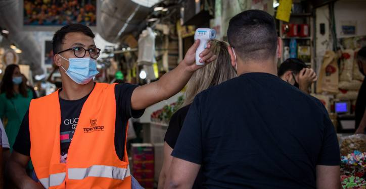 A man checks the temperature of a customer to identify if he have fever at the entrance to the Mahane Yehuda Market in Jerusalem on June 23, 2020. Photo by Nati Shohat/Flash90 *** Local Caption *** ?????? ???? ??????? ?????? ????? ?????? ???? ????? ???