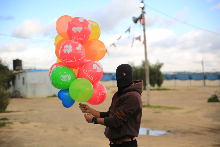 Young Palestinian men prepare a flammable object to be flown toward Israel, near the Israel-Gaza border east of Al-Bureij refugee camp in the central Gaza Strip on February 10, 2020. Photo by Ali Ahmed/Flash90  *** Local Caption *** ??? ?????? ????? ????? ???? ??????? ???????? ????? ??? ????