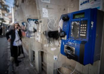 An Ultra Orthdox Jewish man uses a public pay phone in the street, in the ultra orthodox Mea Shearim neighbourhood in Jerusalem, on April 8, 2018. Photo by Yonatan Sindel/Flash90 *** Local Caption *** ??? ????? ?????  ??????  ???? ????? ??? ?? ??? ??? ??????? ???? ????????? ?????????? ???? ????? ?????? ????? ???