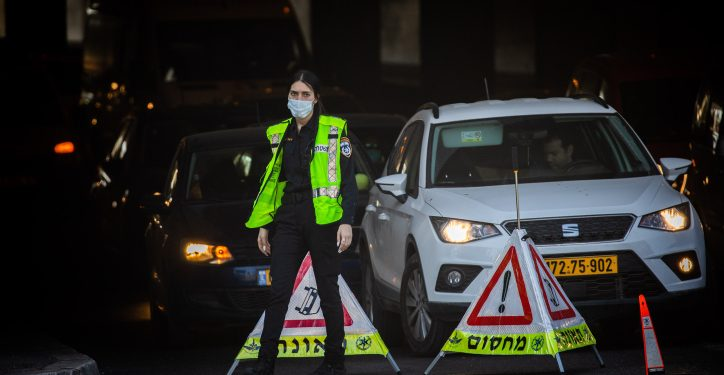 Police at a termporary roadblock in Jerusalem on January 10, 2021, during a 3rd nationawide full lockdown, in an effort to prevent the spread of the Coronavirus. Photo by Yonatan Sindel/Flash90 *** Local Caption *** ??? ???? ??????? ?? ???? ????? ?????? ???? ???