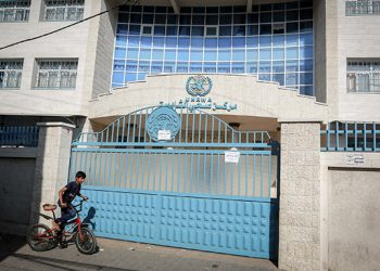 Palestinians walk past the closed offices of United Nations Relief and Works Agency (UNRWA) during a strike of all UNRWA institutions in Rafah in the southern Gaza Strip on September 24, 2018. Washington has provided more than $350 million a year for the agency which helps Palestinian refugees, but US President Donald Trump pulled all funding earlier this year. Photo by Abed Rahim Khatib/ Flash90
