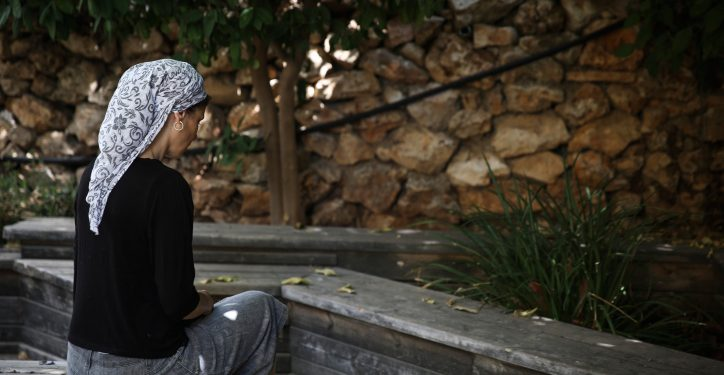 An Orthodox Jewish woman sits in the garden of the abused women's shelter in Beit Shemesh, July 15, 2014. The shelter is a home for women who have suffered physical abuse from their husbands, and their children. Photo by Hadas Parush/Flash90 *** Local Caption *** ???? ???? ???? ????? ????? ??? ??? ????? ???????