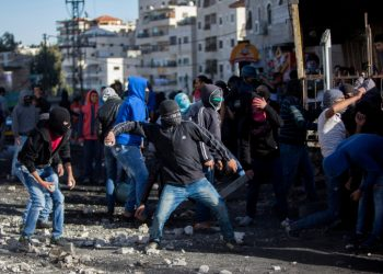 Palestinian youths throw stones during clashes with Israeli Border Police in the Shuafat Refugee Camp, in Jerusalem, following Friday prayers on November 7, 2014. Sporadic clashes continued over access to Jerusalem's al-Aqsa Mosque in the Old City with Border Police shooting tear gas and some rubber bullets to quell Palestinian youths from throwing stones. Photo by Yonatan Sindel/Flash90 *** Local Caption *** ????? ????? ??????? ???? ????? ????? ????? ?????? ????????