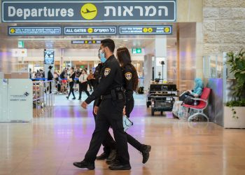 Israeli police officers enforce the COVID-19 regulations at the Ben Gurion International Airport, on July 19, 2021. Photo by Avshalom Sassoni/Flash90 *** Local Caption *** בן גוריון שדה תעופה קורונה מטיילים יוצאים שוטרים  אכיפה
